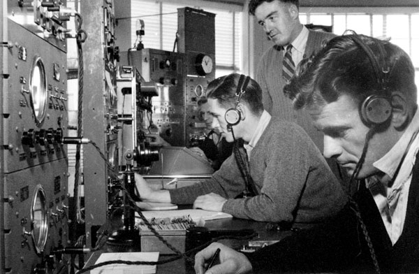 Operators at Auckland Radio ZLD. L-R: G Haywood (in background on Marconi MW Direction Finding), George Haines on 500kHz radiotelegraph watch, Carl Little John (standing) and J Thompson (?) on 2182kHz watch.