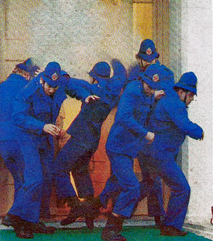 Police storm the mansion's front door in Terry and the Gunrunners