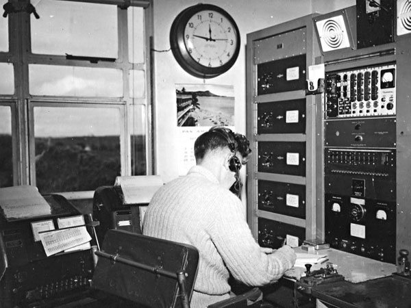 Radio operator Andy Bennie at work in the Air/Ground communications room at Musick Memorial Radio Station, circa 1959