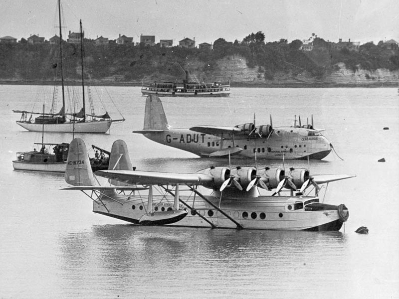 Pan American Airways flying boat 'Samoan Clipper' (foreground), and Imperial Airways flying boat 'Centaurus', moored off the Pan American wharf at Mechanics Bay, Dec 1937.